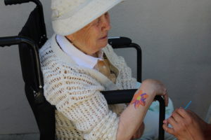 A participant showing off the beautiful flower she had painted on her arm
