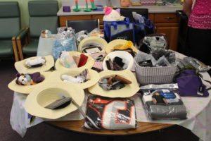 Photo of the prizes for the Alzheimer's room, includes some sun hats, stuffed animals, and blankets