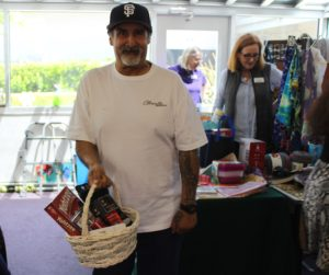 A participant shows off his basket of prizes from the carnival, which includes a Yahtzee game