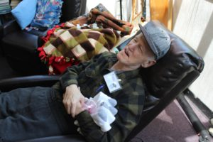 A participant lounges in a chair cradling the new socks he won from the carnival
