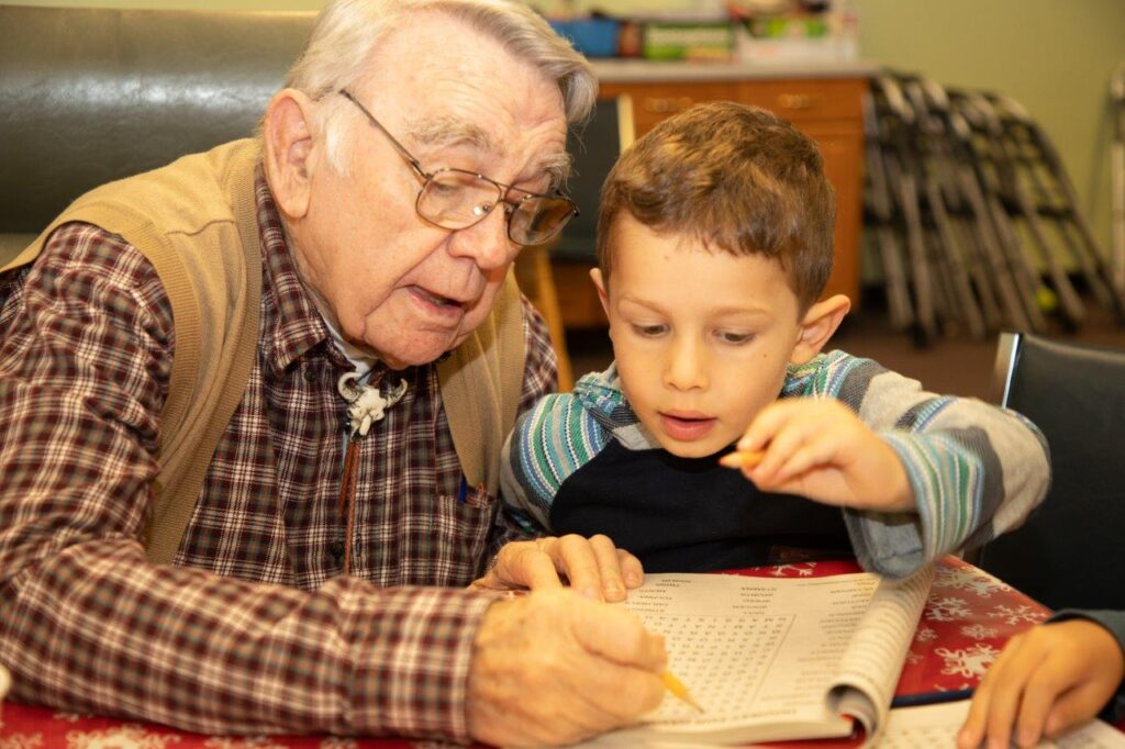 Senior gentleman playing a word puzzle game with a young boy.