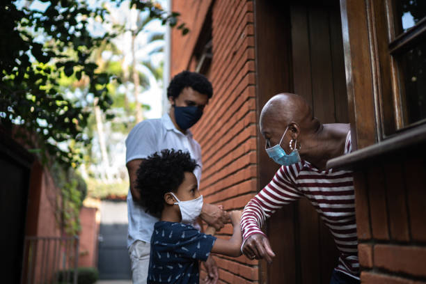 Photo of a young kid and an adult visiting an older adult at the doorway with masks on.