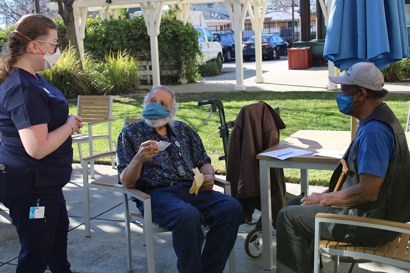 Two guys sitting at an outdoor table talking to a woman with everyone wearing masks.