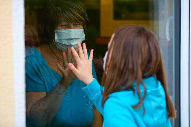 Grandmother and granddaughter touch hands on window while on visit. Senior woman staying at home in time of quarantine for coronavirus or Covid-19.
