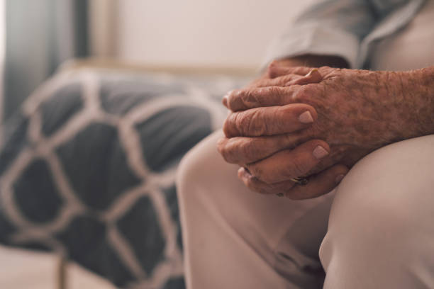 Cropped shot of a senior woman sitting with her hands clasped in a retirement home