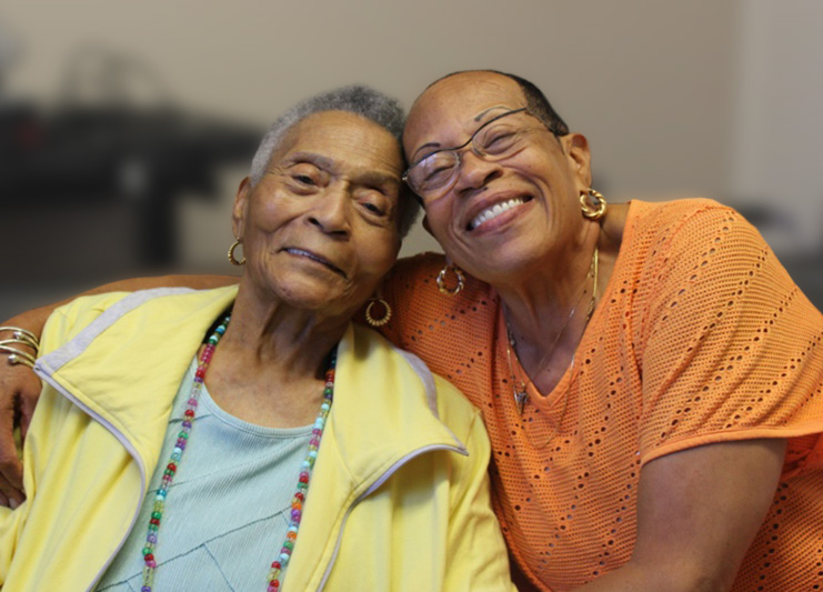 Two ladies smiling and sitting together.